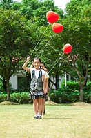 Three children standing in a row and holding balloon together