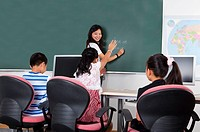 Child, Young teacher teaching three children and smiling