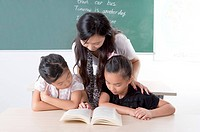 Child, Young teacher teaching children and reading book together