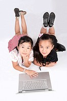 Child, Two girls lying on front with laptop and looking up together