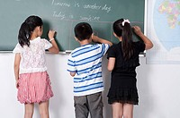 Child, Children standing in a row and writing on the blackboard together