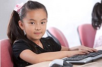 Child, Girl using computer and looking at the camera with smile