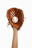 Human hand wearing baseball glove and holding a baseball