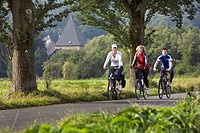 three persons cycling on the Ruhr Valley Cycleway, Kemnade castle in the background, Germany, North Rhine_Westphalia, Ruhr Area, Witten