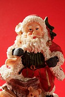 Santa Claus figurine over red background, studio shot