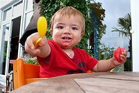 little boy with smudgy mouth in a child seat pointed a spoon towards the camera