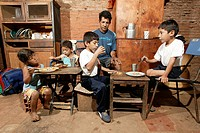 Guarani family eating, single father, in the poor area of Chacarita, Asuncion, Paraguay, South America
