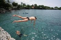 Swimmer jumping in the Captain Cook's bay on Big Island, Hawaii, USA