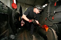 Engine driver fuelling the tank of an historical steam train