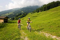 Two women riding mountain bikes, Amoseralm, Dorfgastein, Gastein Valley, Salzburg, Austria