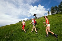 Three hikers walking over a meadow, crucifix above, Grossarl Valley, Salzburg, Austria