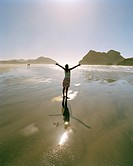 Woman standing in the shallow water at Wharariki Beach, northwest coast, South Island, New Zealand