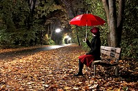 Woman sitting on bench, holding umbrella