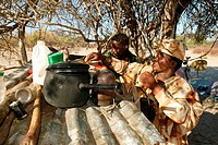 Woman storing food and dishes on corrugated metal roof and tree to protect them from vermin, Cattlepost Bothatogo, Botswana, Africa
