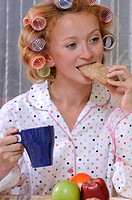 Redheaded woman wearing pajamas with curlers in her hair eating and drinking from blue cup
