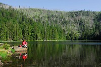 Woman sitting on lake Rachelsee, Bavarian Forest National Park, Lower Bavaria, Bavaria, Germany