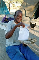 Traditional healer's patient displaying his prescription for medicinal herbs, Sehitwa, Botswana, Africa
