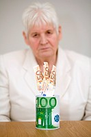 Senior woman with Euro banknotes in a savings bank in the form of a 100 Euro banknote.