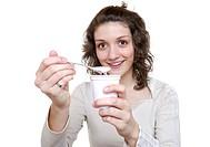 Young woman eats a yoghurt