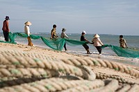 Fishermen with fishing net on the beach of Mui Ne, Binh Thuan Province, Asia