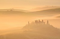 hilly landscape with farmhouse in morning mist, Italy, Tuscany