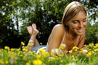 Woman lying in a meadow full of flowers, Relaxation, South Tyrol, Italy