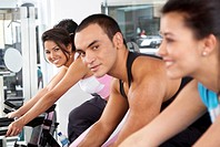 people at the gym working out on the cycling machines