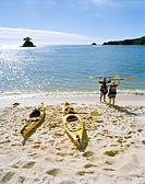 Seakayaking, people with paddle standing on the beach at Torrent Bay, north coast, Abel Tasman National Park, South Island, New Zealand