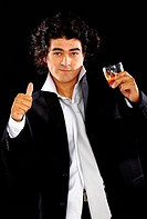 young alcoholic man with whiskey glass in his hand celebrating his success