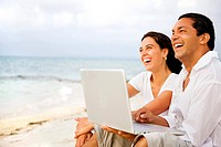 couple with laptop on the beach