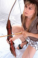 blond young woman in tight shorts kneeing and holding bow and arrow