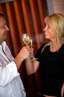 middle_aged man and woman clinking glasses with sparkling wine