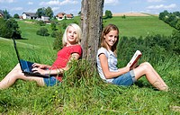 teenage girls sitting in meadow and using laptop