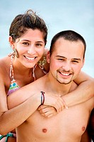happy young couple at the beach, the woman embraces her boy_friend from behind