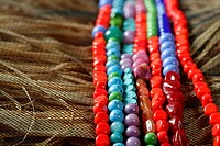 Color stones jewelry necklaces over natural straw and tulle background