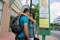 Florida, Miami Beach, bus stop, public transportation, route, map, info, information, schedule, fare, sign, signboard, guide, man, woman, couple, rela...