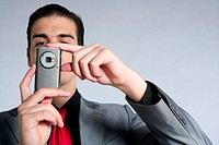 Businessman with gray suit taking photos with phone camera