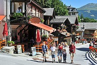 Tourists walking in street with traditional wooden houses / chalets and hotels in the Alpine village Grimentz, Valais, Switzerland