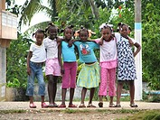 Group of small girls holding each other and smiling into camera, Haiti, Grande Anse, Dame Marie