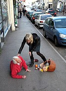 Elderly woman being helped after falling on a street.