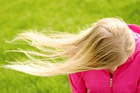 The hair of a young blonde woman blow in the wind