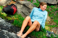 Female hiker cooling her feet in a mountain stream, USA, Oregon