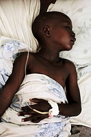 Child patient lying in a hospital bed, with a drip attached to his hand. Photographed at St. Mary´s Hospital in Lacor, Gulu, Uganda.