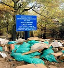Dumped rubbish next to flytipping sign, in a public woodland area. The sign refers to the 1990 Environmental Protection Act, that was passed in the UK...