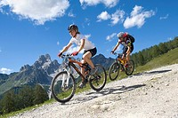 man and woman with mountain bikes on a tour in the alpine mountains, Austria, Upper Austria, Gmunden