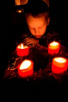 Little boy sitting in front of advent wreath