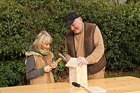 nest box construction, grandpa and grandson assembling wooden nest box , Germany