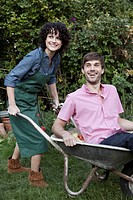 A woman pushing a man in a wheelbarrow