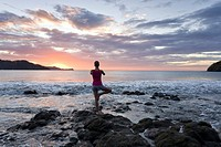 Young woman doing yoga at sunset in front of ocean surf at Playas del Coco, Costa Rica