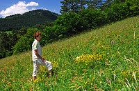 Woman looking at plants on a round tour on the orchid natur trail Erlingsbach, Switzerland